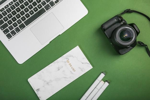 Área de trabalho de escritório com um laptop e uma câmera fotográfica