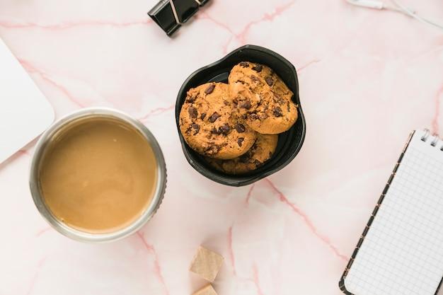 Área de trabalho de escritório com uma xícara de café e biscoitos