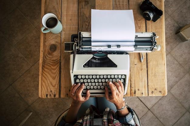 Área de trabalho de madeira com máquina de escrever vintage e mãos de mulher trabalhando nela para escrever