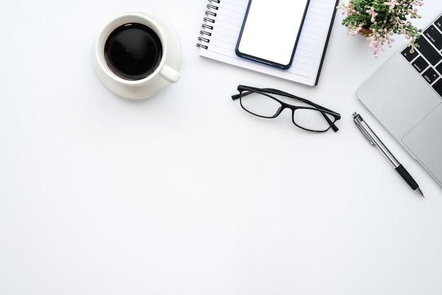 Área de trabalho de mesa branca de vista superior com espaço de cópia de caneca de café de teclado de smartphone de óculos.