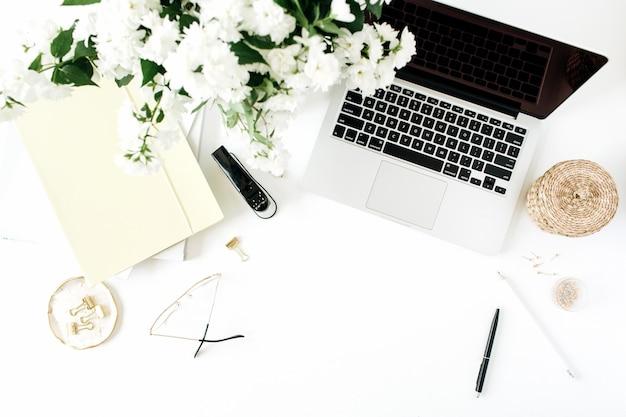 Área de trabalho de mesa de escritório com laptop, buquê de flores e artigos de papelaria na mesa branca