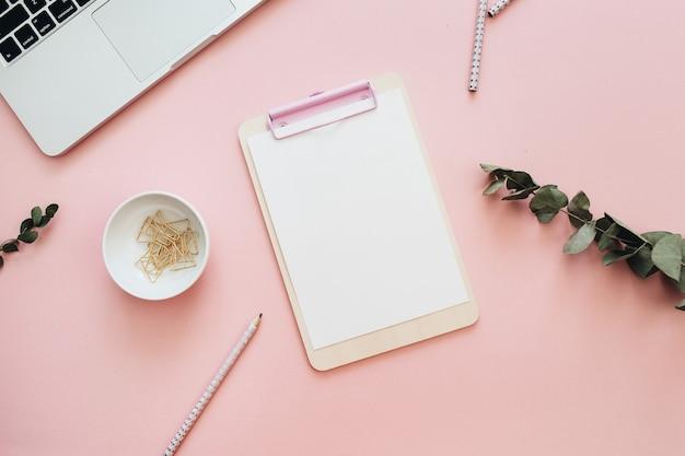 Área de trabalho de mesa de escritório em casa plana com laptop, área de transferência e galhos de eucalipto em fundo rosa pastel