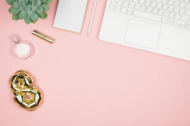 Área de trabalho de mulher com laptop, perfume, folha de ouro ballon 8 e copyspace. vista do topo. feliz dia das mulheres. 8 de março, parabéns.