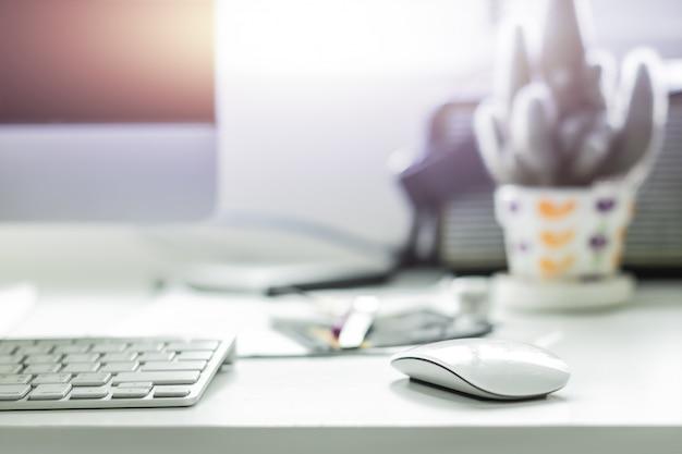 Área de trabalho do computador com teclado branco e mouse na mesa de trabalho