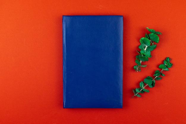 Área de trabalho do escritório com maquete de caderno de couro azul, fundo de mesa vermelho com flor seca, vista de cima e foto plana