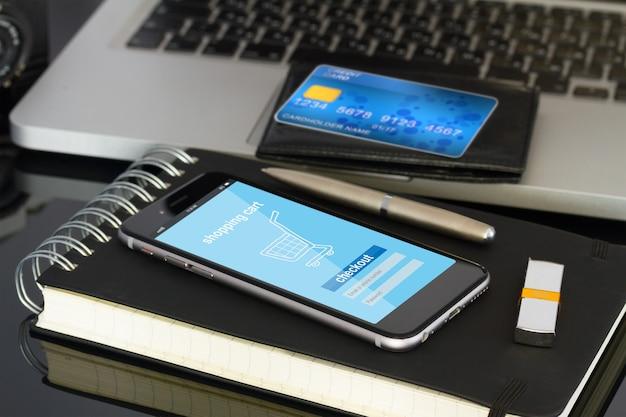 Área de trabalho do escritório com página da loja na internet no celular e cartão de plástico