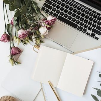 Área de trabalho do escritório em casa do chefe da senhora leiga plana com caderno de folha de papel em branco, laptop, buquê de flores de rosas, ramo de eucalipto na mesa branca
