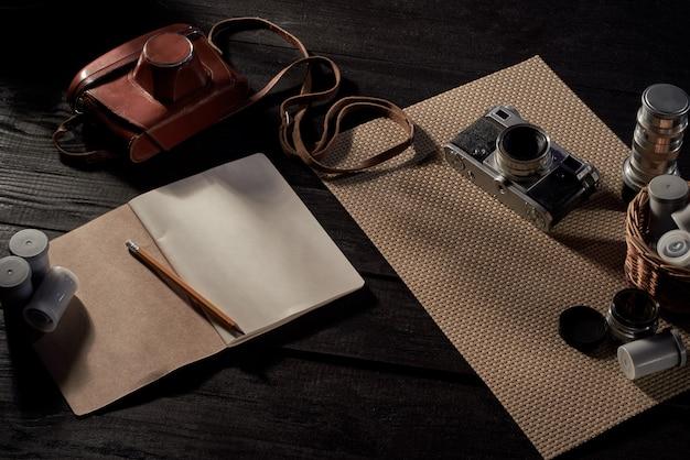 Área de trabalho do fotógrafo. câmera de filme, lentes, capa, filme de 33 mm, caderno e lápis.