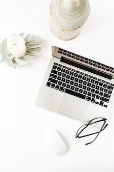 Área de trabalho mínima na mesa do escritório em casa com laptop, óculos brancos