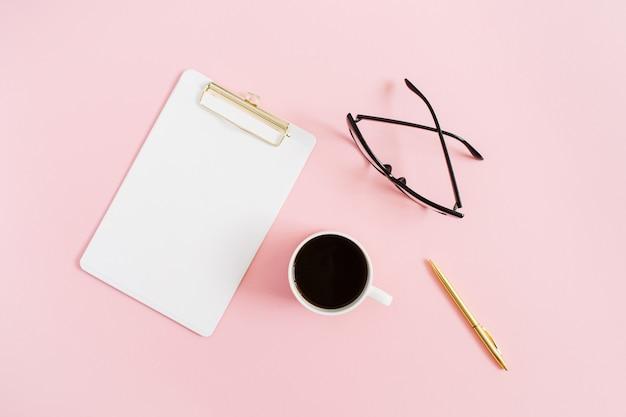 Área de trabalho mínima para mulheres em casa com prancheta, caneta, caneca de café e óculos rosa