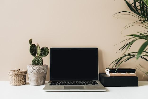 Área de trabalho minimalista em uma mesa de escritório em casa com laptop, cacto, palma em bege