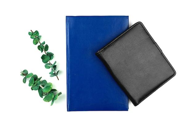Área de trabalho plana, espaço de trabalho de escritório com cadernos de couro e flores verdes secas, composição floral, conceito de maquete e foto de vista superior em um fundo branco isolado