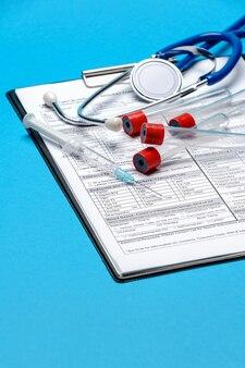 Área de transferência com o formulário em branco de papel com ferramentas médicas sobre fundo azul com espaço para lidar.