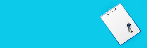 Área de transferência com uma folha em branco e as chaves da casa ou apartamento em um fundo azul. bandeira. camada plana, vista superior.