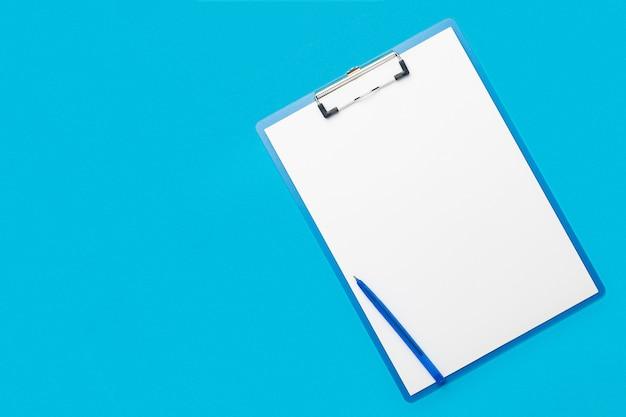 Área de transferência com uma folha em branco e uma caneta sobre um fundo azul claro. questionário de conceito, formulário, contrato. bandeira. camada plana, vista superior.