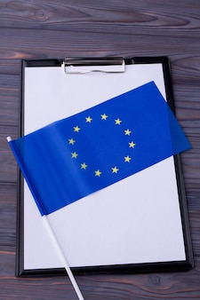 Área de transferência em branco e bandeira azul da ue na mesa cinza de madeira