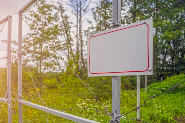 Área proibida cercada com uma cerca de arame farpado. portão com cadeado fechado para a chave