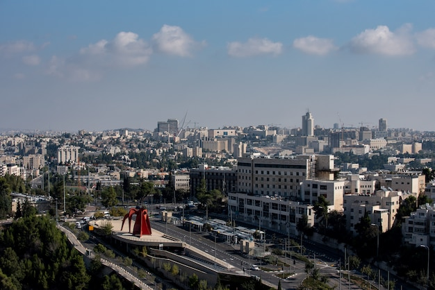 Área urbana cercada por construções verdes e estradas sob a luz do sol e céu nublado