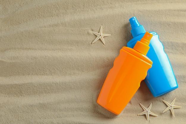 Areia clara do mar com estrela do mar e protetores solares, espaço para texto. fundo de férias de verão