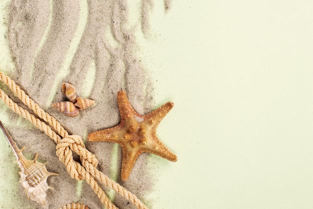 Areia com corda náutica e estrela do mar