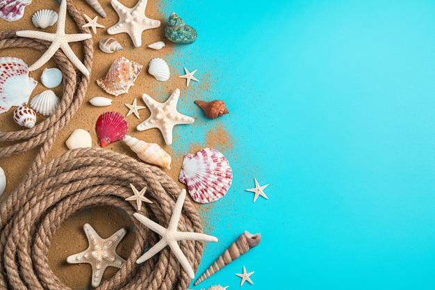 Areia, conchas e corda em um fundo azul com espaço de cópia