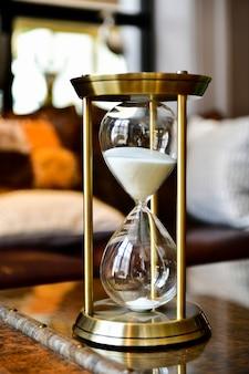 Areia correndo através das lâmpadas de uma ampulheta, medindo o tempo que passa na sala de estar.