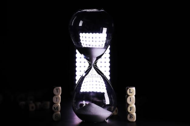 Areia correndo pelas lâmpadas de uma ampulheta medindo o tempo que passa em uma contagem regressiva para um prazo, em um fundo de mesa escuro com espaço de cópia.