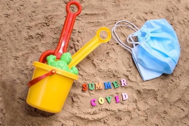 Areia da praia, brinquedos infantis de areia, máscaras. coronavírus de verão.