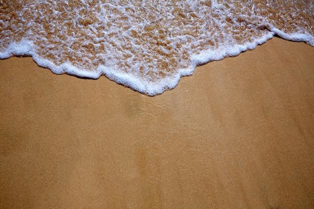 Areia da praia das ilhas canárias e textura da onda