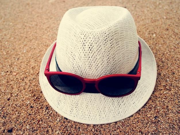 Areia da praia dos óculos de sol do chapéu relaxa férias