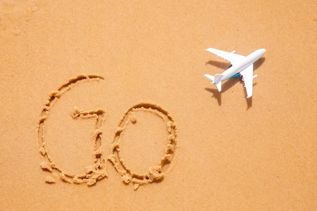 Areia da praia escrita '' go '' com um avião de brinquedo ao lado. conceito de viagens