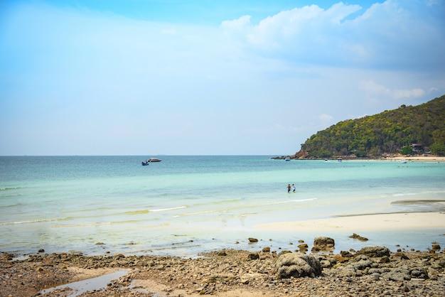 Areia da praia tropical mar verão ilha azul água céu brilhante com fundo da rocha colina