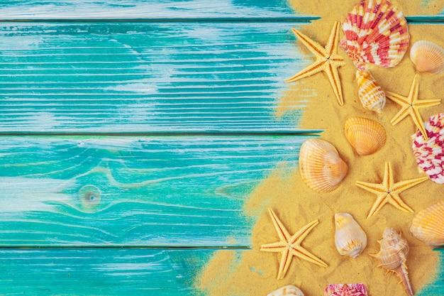 Areia do mar e conchas do mar no chão de madeira azul