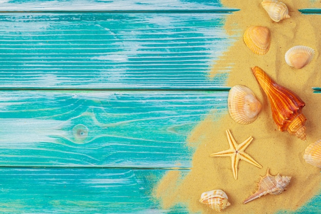 Areia do mar e conchas do mar sobre fundo azul de madeira