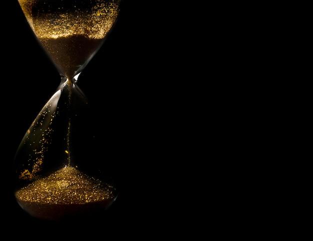 Areia e glitter dourado passando através dos bulbos de vidro de uma ampulheta medindo o passe