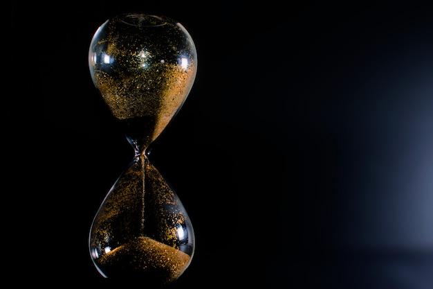 Areia e glitter dourado passando através dos bulbos de vidro de uma ampulheta.