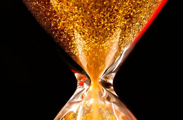 Areia e glitter dourado passando através dos bulbos de vidro de uma ampulheta