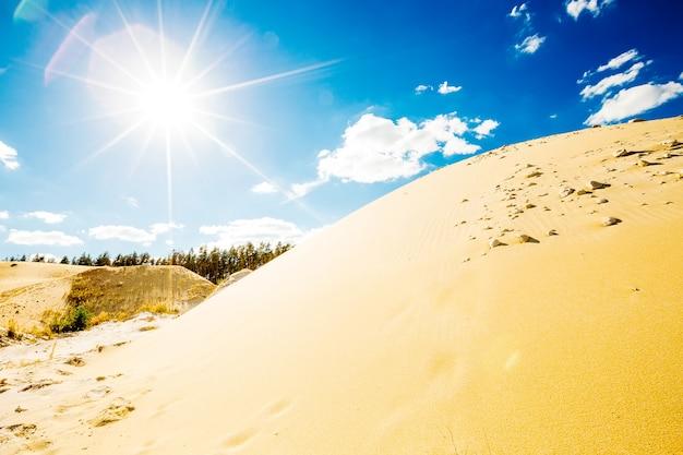 Areia iluminada pelo sol brilhante do meio-dia no céu azul