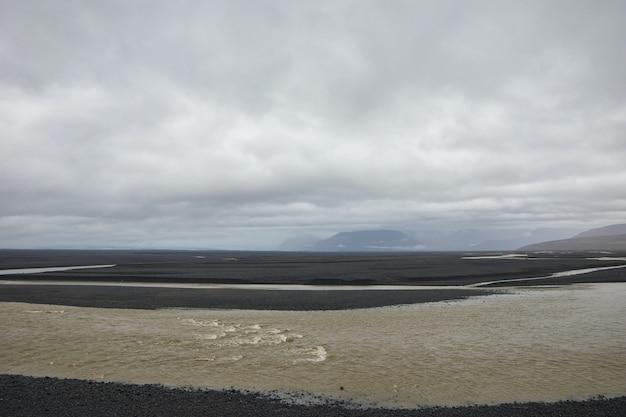 Areia marrom sob nuvens brancas