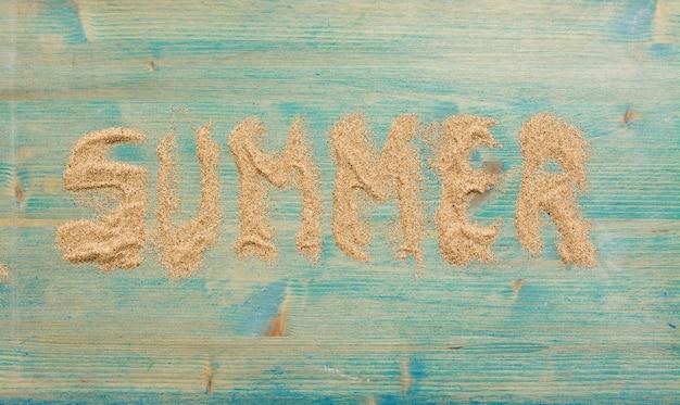 Areia na madeira planked azul com a palavra verão.