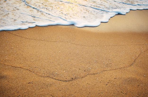 Areia na praia à beira-mar ao nascer do sol