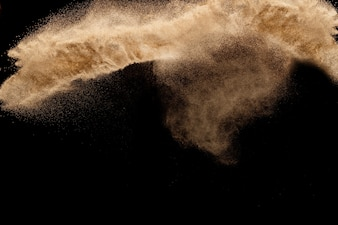 Areia seca do rio com explosão de pedra. Fundo colorido amarelo da obscuridade do agianst do respingo da areia.