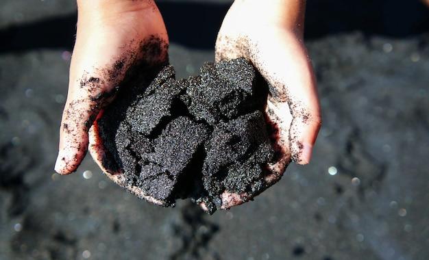 Areia vulcânica preta nas mãos de criança, lanzarote, ilha