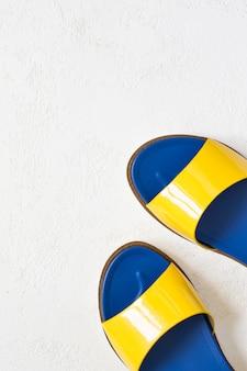 Areias envernizadas azuis amarelas brilhantes do verão da juventude fêmea em um fundo branco.
