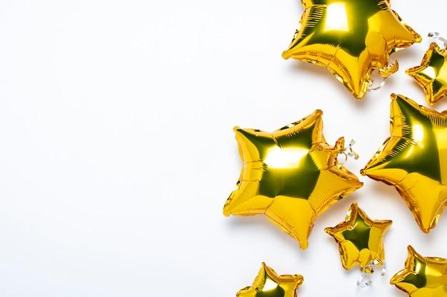 Areje balões dourados star a forma e os doces em um fundo branco.