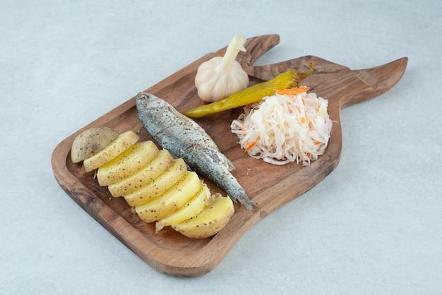 Arenque, batata cozida e picles misturados na placa de madeira.