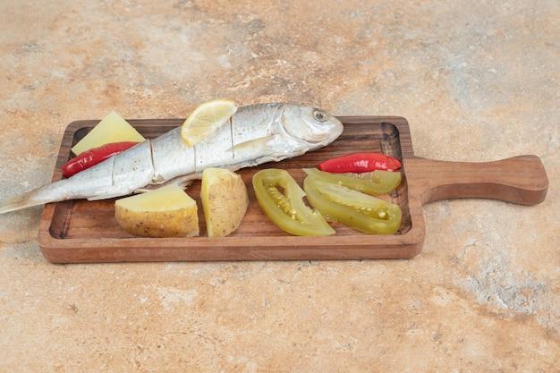 Arenque com batata cozida e picles em tábua de madeira