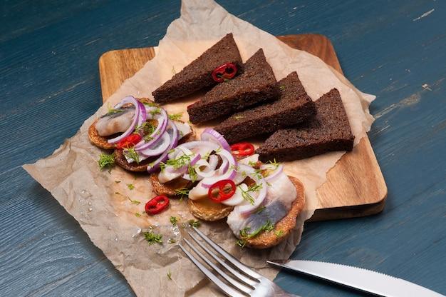 Arenque com batata, pão preto e pimenta malagueta