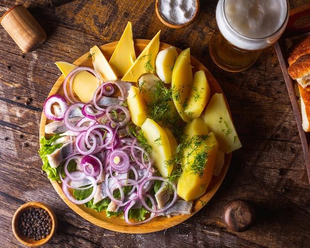 Arenque com batatas com cebola, manteiga e verduras, servido com cerveja 1