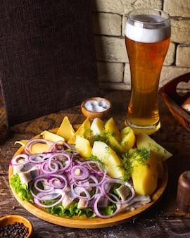 Arenque com batatas com cebola, manteiga e verduras, servido com cerveja